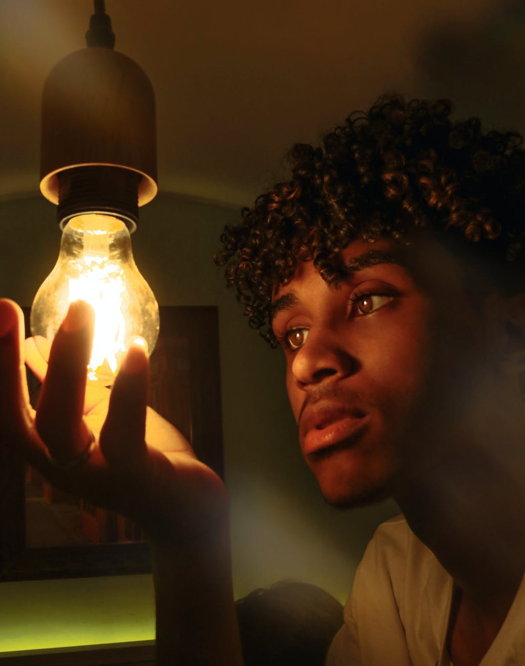 black man changing light bulb